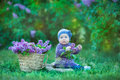 Smiling baby girl 1-2 year old wearing flower wreath, holding bouquet of lilac outdoors. Looking at camera. Summer spring time. Royalty Free Stock Photo
