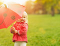 Smiling baby looking out from red umbrella Royalty Free Stock Photo