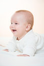 Smiling baby lying on the blanket cute orange background Royalty Free Stock Photography