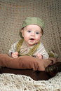 Smiling baby months in a cap lying on his st stomach the retro suitcase Royalty Free Stock Photography