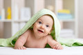 Smiling baby after shower or bath with towel on Royalty Free Stock Photo
