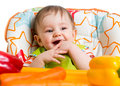 Smiling baby sitting in chair ready to eat high Stock Image