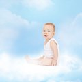 Smiling baby sitting on the cloud Stock Photo