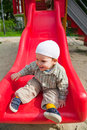 Smiling baby on slide boy a red in a summer day Royalty Free Stock Images