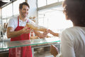 Smiling baker doing loaf transaction with customer at the bakery Stock Image