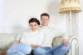 Smiling barefoot husband and wife in jeans sit on white sofa at home Royalty Free Stock Photo