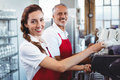 Smiling barista using the coffee machine with colleague behind