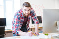 Smiling bearded man standing and working on blueprint in office Royalty Free Stock Photo