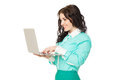 Smiling beautiful brunette girl in green skirt and blouse holdin slim holding laptop over white background Royalty Free Stock Images