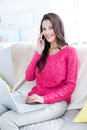 Smiling beautiful brunette speaking on the phone while using laptop in living room Stock Photography