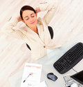 Smiling beautiful business woman relaxing at desk Stock Image