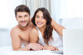 Smiling beautiful couple using laptop and looking at camera Royalty Free Stock Photo