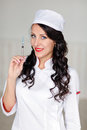 Smiling beautiful doctor woman with red lips and a syringe in hi Royalty Free Stock Photo