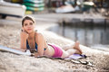 Smiling beautiful fit woman sunbathing in a shorts on a beach enjoying summer holidays young woman lying on beach mat near the sea Royalty Free Stock Photo