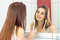 Smiling beautiful girl looks in the mirror and holding a toothbrush Royalty Free Stock Photo