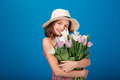Smiling beautiful little girl in hat holding bouquet of tulips standing and over blue background Royalty Free Stock Photography