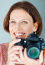 Smiling beautiful mature woman with a SLR camera Royalty Free Stock Image