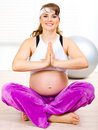 Smiling beautiful pregnant woman doing yoga Stock Photos