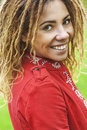 Smiling beautiful woman with dreadlocks young in red clothes closeup Royalty Free Stock Photography