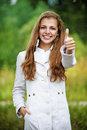 Smiling beautiful woman lifts thumbs upwards young against background of autumn park Stock Images