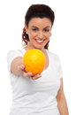 Smiling beautiful woman offering you an orange Stock Images