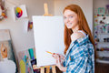 Smiling beautiful woman painter making sketches on blank canvas young with long red hair in artist workshop Stock Photo