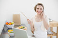 Smiling beautiful woman phoning while standing in the kitchen in front of her laptop at camera Stock Images