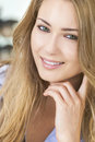 Smiling beautiful woman resting on hand portrait of a blond young with green eyes and her Stock Image