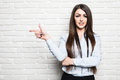Smiling beautiful woman standing and points finger towards, white brick wall on background Royalty Free Stock Photo