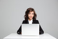 Smiling beautiful young woman sitting and using laptop curly in black jacket Royalty Free Stock Photography