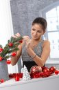 Smiling beauty decorating for christmas tree with red bulb and garland Stock Photos
