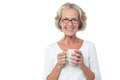 Smiling bespectacled old lady drinking coffee senior with hot in front of camera Stock Photography