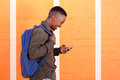 Smiling black guy walking with bag and mobile phone Royalty Free Stock Photo