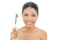 Smiling black haired model holding eyebrow brush on white background Royalty Free Stock Images