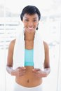 Smiling black haired woman wearing a towel around her neck in living room Royalty Free Stock Photo