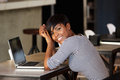 Smiling black woman sitting at cafe with laptop