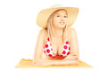 Smiling blond female with hat lying on a beach towel and posing isolated white background Stock Photos