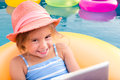 Smiling blond girl floating on yellow inner tube Royalty Free Stock Photo