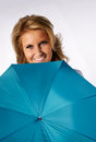 Smiling blond girl hiding behind her umbrella studio shot beautiful woman looking camera Stock Photo