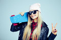Smiling blond teenager girl in black sunglasses and pink hat with blue skateboard. on white background