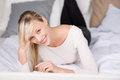 Smiling blond woman lying in bed at her room Royalty Free Stock Image