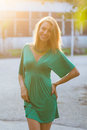 Smiling blond woman in sunlight young blonde standing wearing green dress Stock Images
