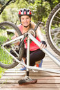 Smiling blonde athlete checking her mountain bike Royalty Free Stock Photo