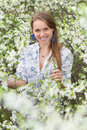 Smiling blonde in blooming garden wearing white blouse posing Royalty Free Stock Photography