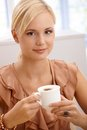 Smiling blonde drinking cappuccino holding coffee cup looking at camera Stock Image