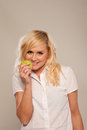 Smiling blonde with green apple Stock Photos