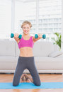 Smiling blonde lifting dumbbells on exercise mat at home in the living room Stock Photo