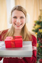 Smiling blonde wearing earmuffs while holding gifts Fotografia de Stock Royalty Free