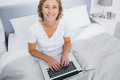 Smiling blonde woman in bed using her laptop looking at camera bedroom at home Stock Photos