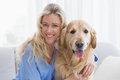 Smiling blonde woman hugging her golden retriever Royalty Free Stock Photo